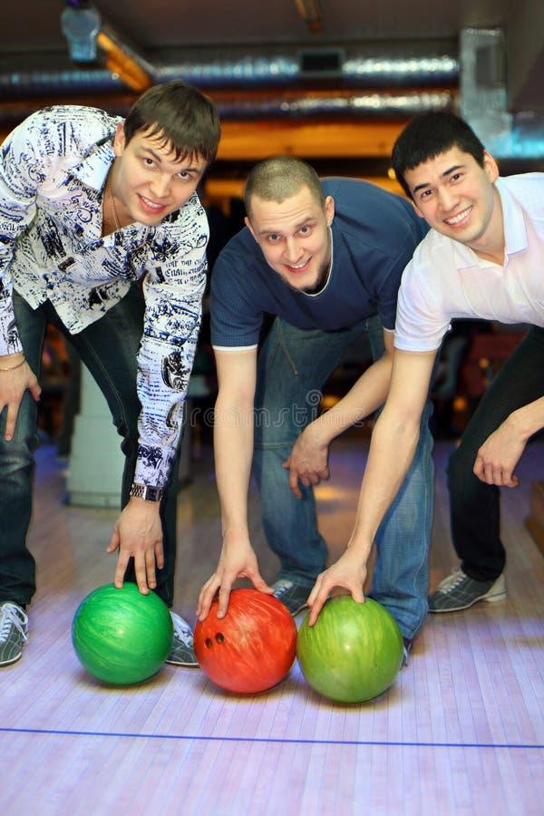 Drei Männer verbogen vorbei, um herauf Kugeln für Bowlingspiel zu heben stockbild