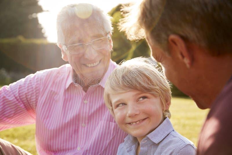 Drei männliche Generationen einer Familie, die in einem Garten sitzt lizenzfreies stockbild
