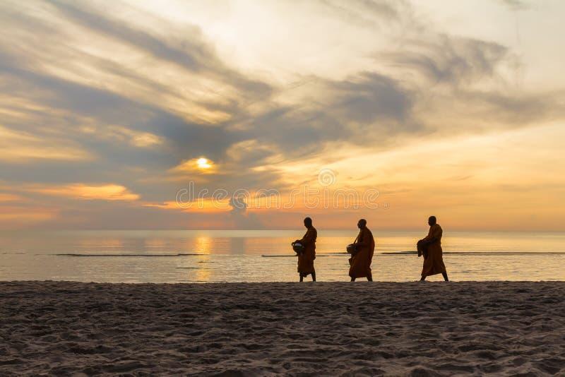 Drei Mönche gehen auf Strand stockbild