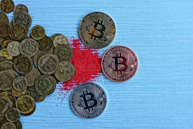 Drei Münzen bitcoin auf einer blauen Tabelle und einem roten Sand an einem Stapel von Münzen lizenzfreies stockbild