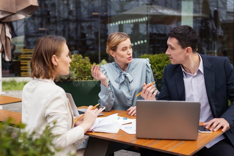 Drei Manager, die Debatte über Geschäftsantrag haben lizenzfreies stockfoto