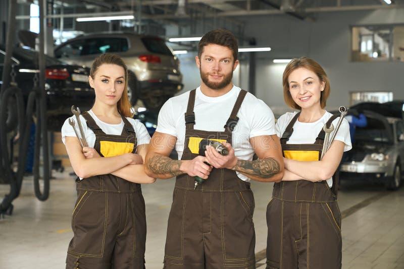 Drei Mechaniker, die zusammen mit Werkzeugen im autoservice aufwerfen stockfotos