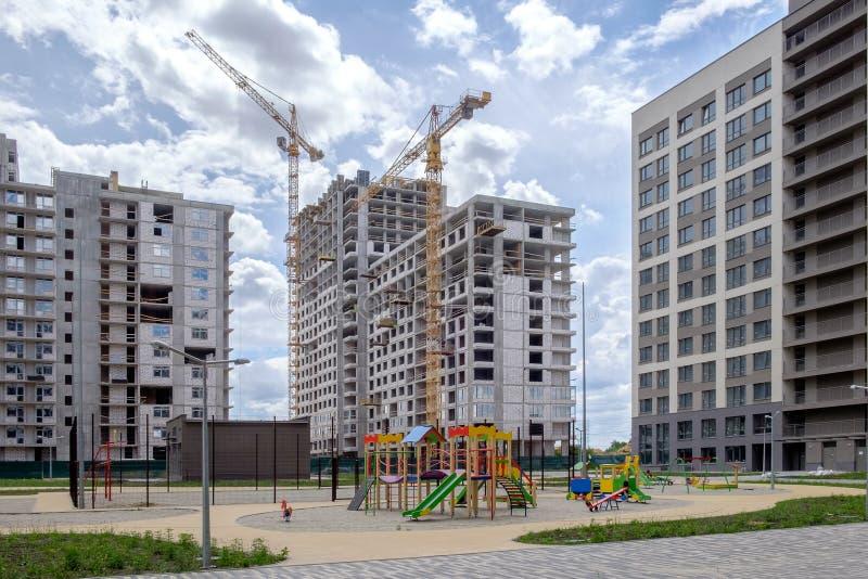 Drei mehrstöckige Häuser, Baukräne, Sport und Kind-` s Spielplatz im eben aufgebauten Bereich von Osteuropa stockbilder