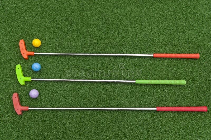 Drei Mini Golf Putters With Balls stockbilder