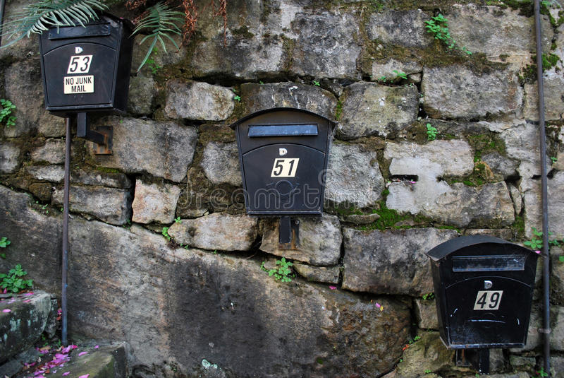 Drei moderne australische Metallpostboxes, die am Steine in den Weg gelegte hängen lizenzfreies stockfoto