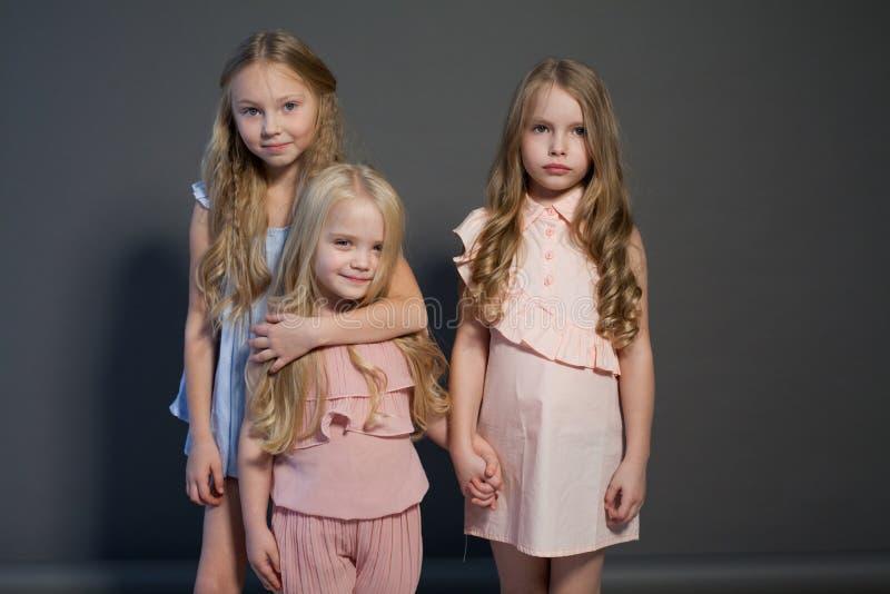 Drei moderne Mädchenfreundinschwestern essen Süßigkeitslutscherkuchen lizenzfreie stockfotografie