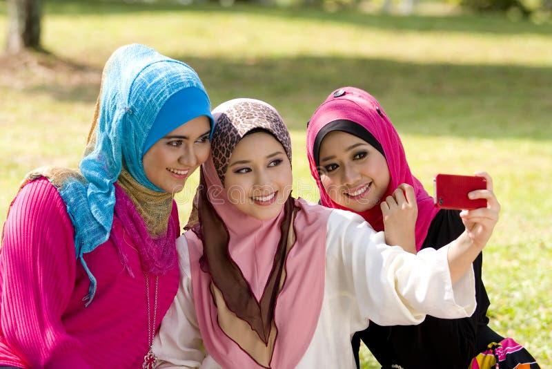 Drei moslemische Mädchen mit Mobiltelefon lizenzfreie stockbilder