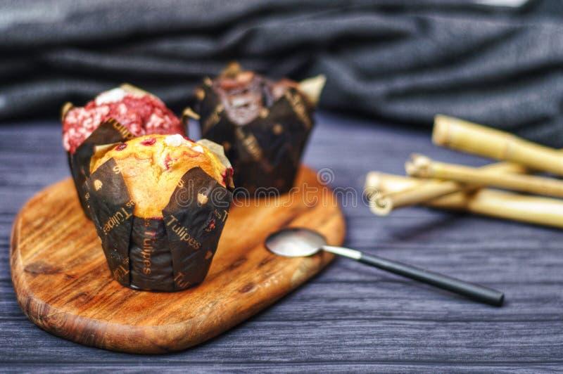 Drei Muffins am hölzernen Schreibtisch stockfotografie