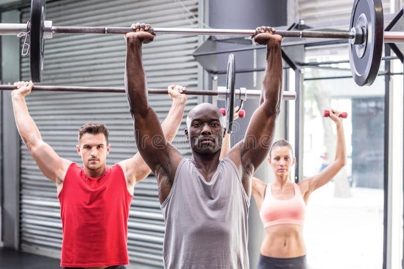 Drei muskulöse Athleten, die Barbells anheben stockbilder