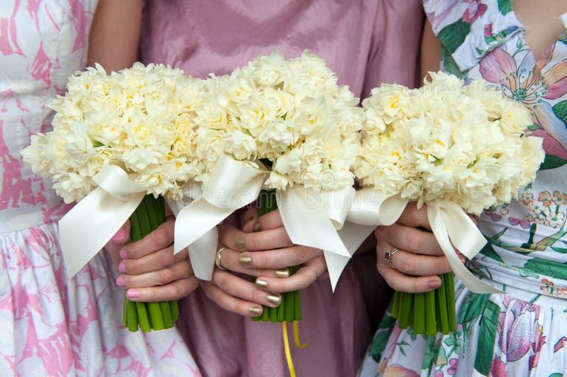 Drei Narzissenhochzeitsblumensträuße gehalten von den Brautjungfern stockfotos