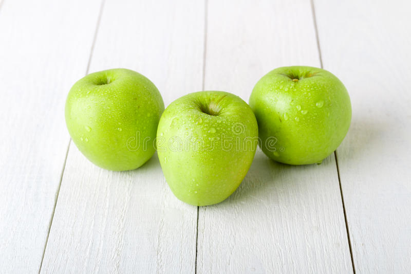 Drei nasse grüne Äpfel auf weißem hölzernem Hintergrund Abschluss oben lizenzfreies stockfoto