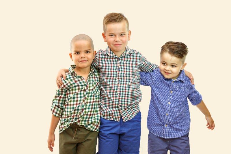Drei nette Jungen der Mode stehen zusammen auf weißem lokalisiertem Hintergrund lizenzfreie stockfotos