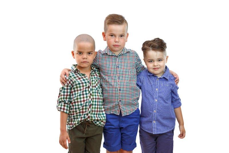 Drei nette Jungen der Mode stehen zusammen auf weißem lokalisiertem Hintergrund lizenzfreies stockfoto