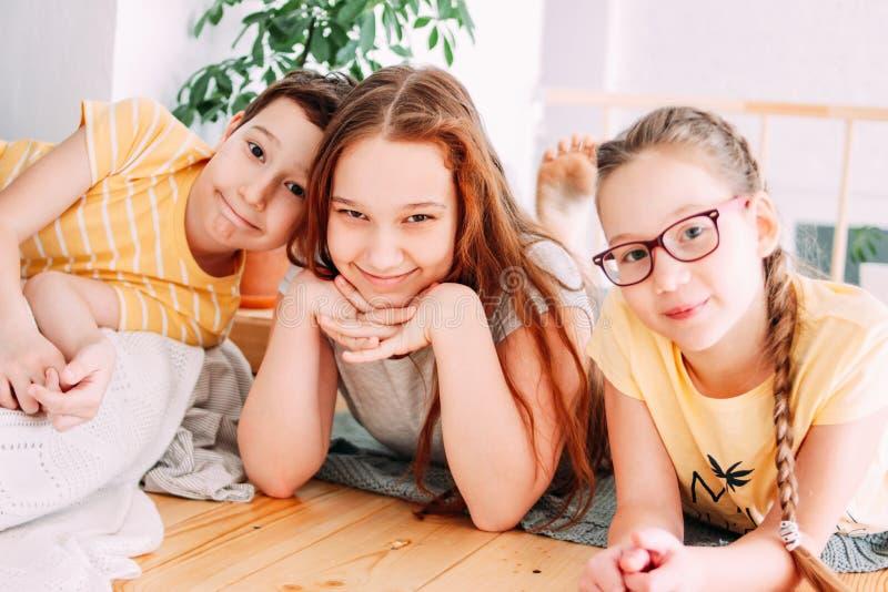 Drei nette lächelnde Kinderfreundtweens, die auf dem Boden liegen lizenzfreies stockfoto