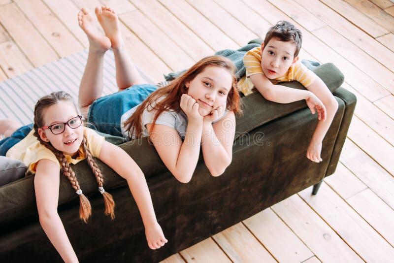 Drei nette lächelnde Kinderfreundtweens, die zu Hause auf Sofa sitzen lizenzfreies stockfoto