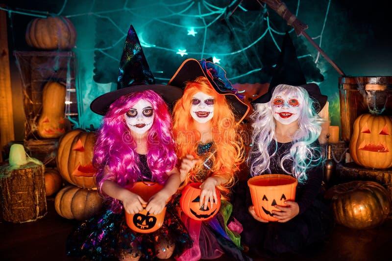 Drei nette lustige Schwestern feiern den Feiertag Lustige Kinder im Karneval kostümiert bereites zu Halloween lizenzfreie stockfotografie