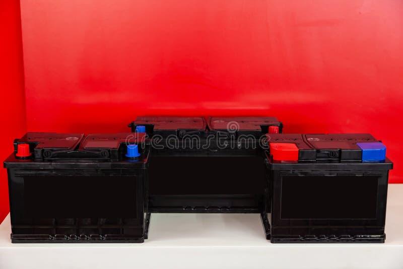 Drei neue schwarze Akkus f?r Auto- und Fahrzeugstand auf einem roten Hintergrund mit wei?en Aufschriften Mechaniker, der innerhal lizenzfreies stockbild