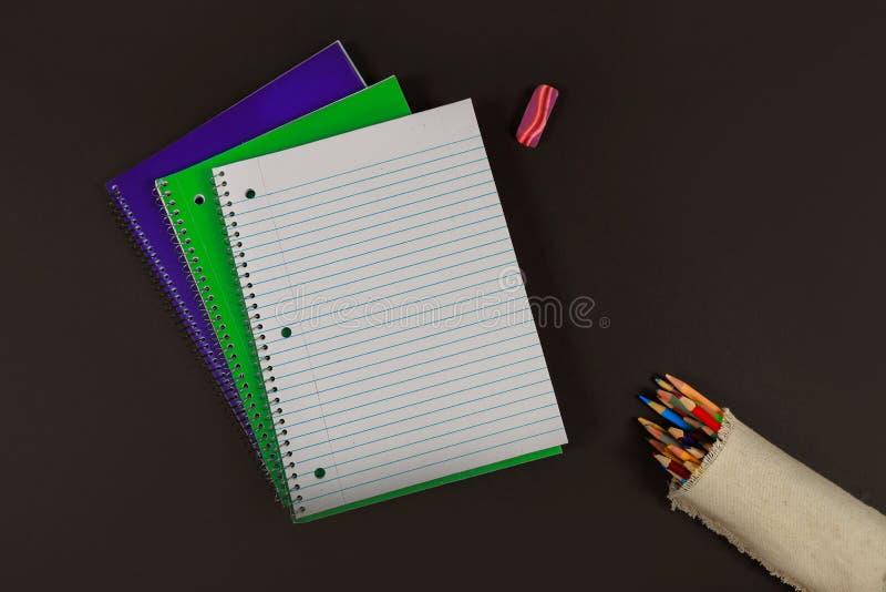 Drei Notizbücher und farbiger Bleistiftschulbedarf lizenzfreie stockfotos