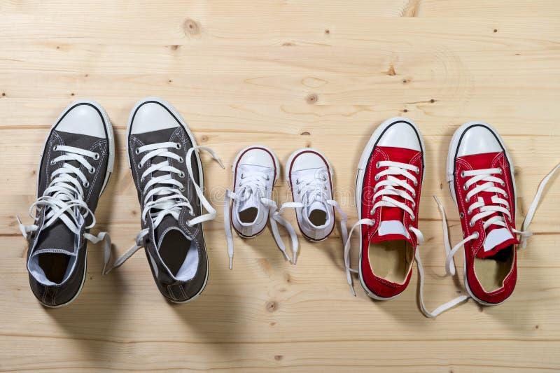 Drei Paare Schuhe im Vater groß, Muttermedium und Sohn oder kleine Größe der Tochter Kinderim Familienzusammengehörigkeitskonzept stockfotografie