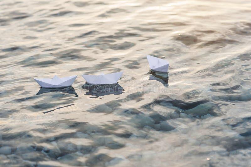 Drei Papierboote, die in Wellen auf dem Wasser bei Sonnenuntergang schwimmen stockfotos
