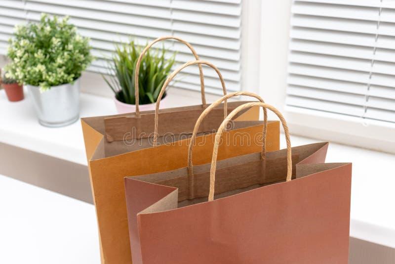 Drei Papiereinkaufstaschen auf wei?em B?rotisch, Onlinehandel und und Lieferungskonzept lizenzfreie stockfotografie