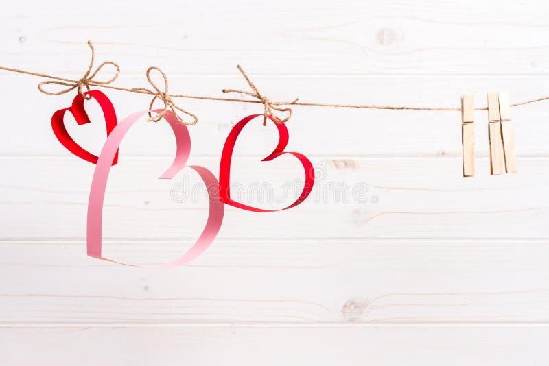 Drei Papierherzen auf dem weißen hölzernen Hintergrund, Konzept für Valentinstaggrußkarte stockfotografie