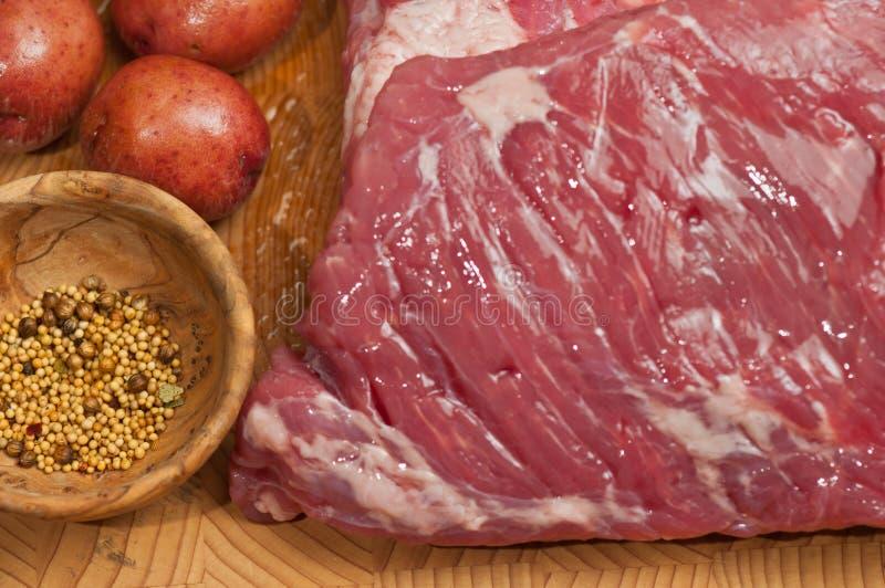 Drei Pfund, rohe, Maisrinderbrust, sechs klein, rot, Kartoffeln und ein Blatt des Kohls, auf einem Bambus, hölzern, Schneidebrett stockbilder