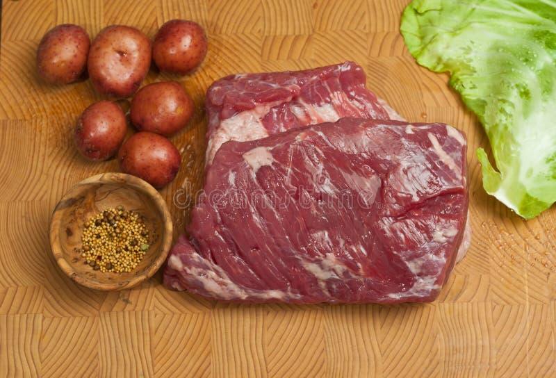Drei Pfund, rohe, Maisrinderbrust, sechs klein, rot, Kartoffeln und ein Blatt des Kohls, auf einem Bambus, hölzern, Schneidebrett lizenzfreie stockfotografie