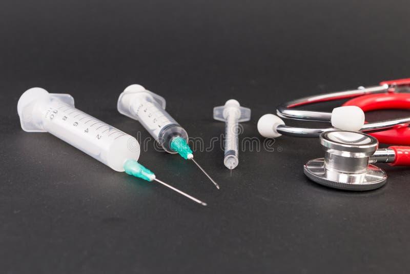 Drei Plastikwegwerfspritzen und Stethoskop stockfotografie