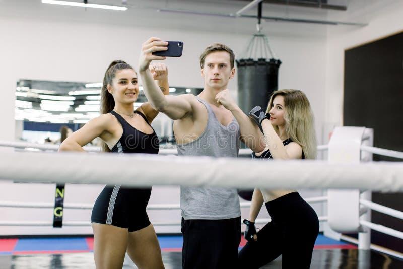 Drei professionl Boxer und Eignungstrainer machen selfie bei der Stellung mitten in Boxring lizenzfreie stockfotografie