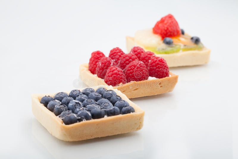 Drei quadratische Kuchen richteten diagonal mit Erdbeeren, raspbe aus lizenzfreies stockbild