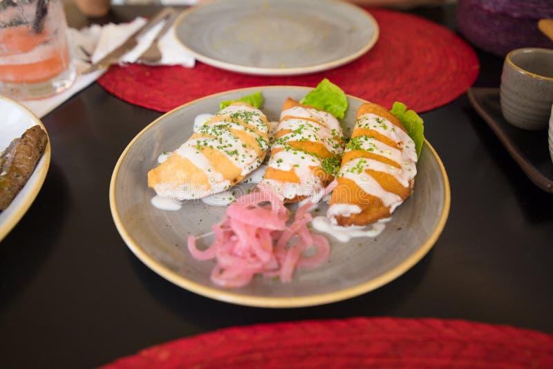 Drei Quesadillas oder Pastetchen im keramischen Teller stockfotos