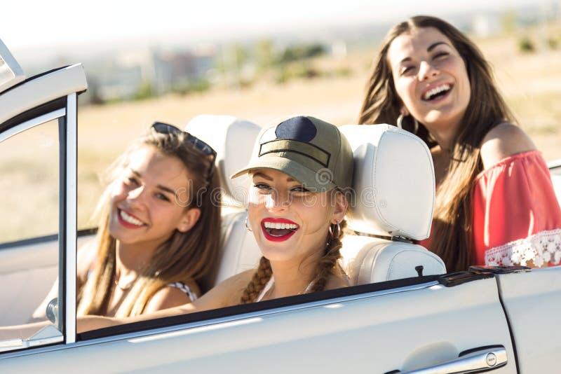 Drei recht junge Frauen, die auf Autoreise auf schönem summe fahren stockfotografie