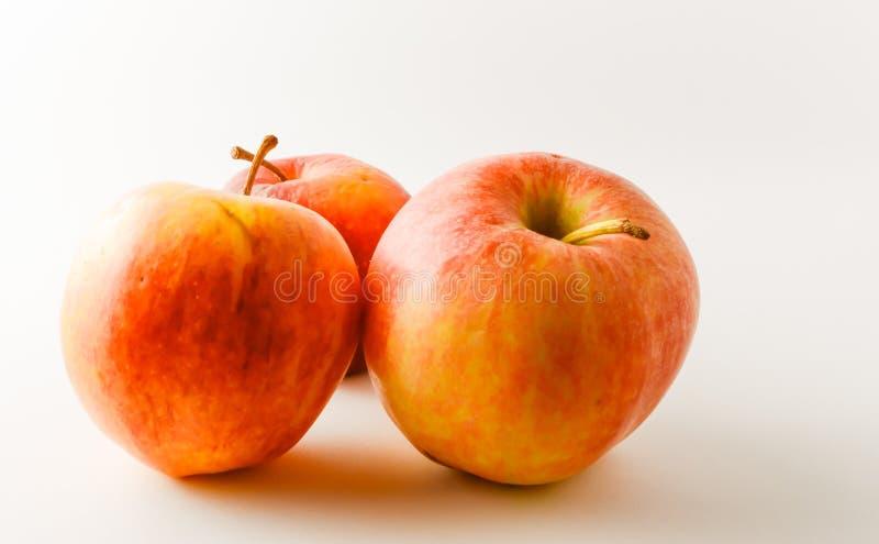 Drei reif, rote, gelbe Äpfel mit Endstück auf weißem Hintergrund stockbilder