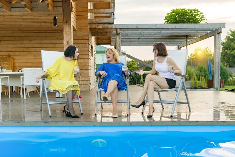 Drei reife Frauen von mittlerem Alter haben den Spaß und Unterhaltung und sitzen in einem Ruhesessel durch das Pool, Sommerabend lizenzfreie stockbilder