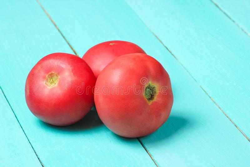 Drei reife Tomaten auf einem blauen Holztisch lizenzfreie stockfotografie