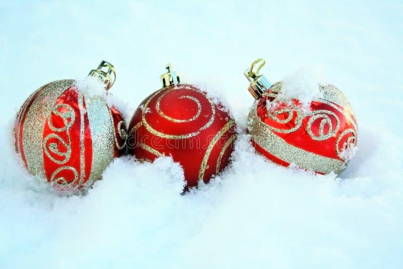 Drei rot und Goldbunte Weihnachtsbälle im Schnee stockfotografie