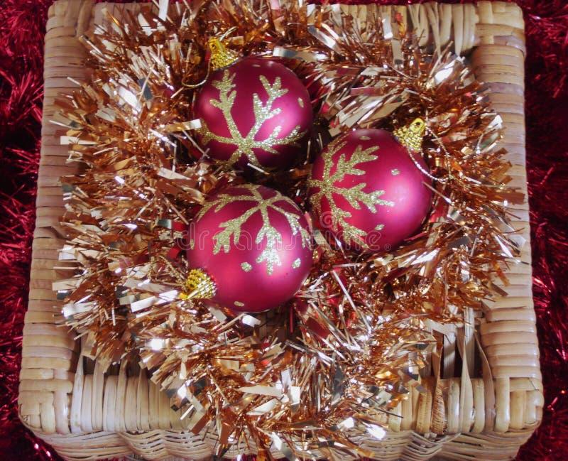 Drei rot und Goldweihnachtsflitter auf Goldlametta im Weidenkasten lizenzfreie stockfotos