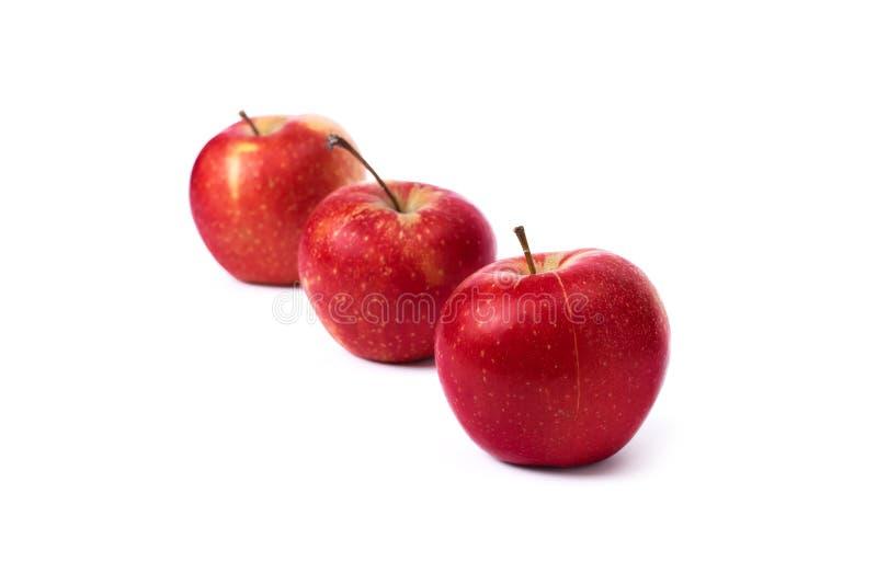 Drei rote ?pfel auf einem wei?en Hintergrund Saftige Äpfel der roten Farbe mit gelben Flecken auf einem weißen Hintergrund stockbild