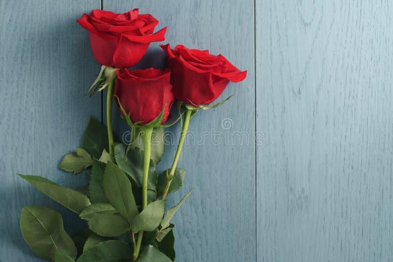 Drei rote Rosen auf Purplehearttabelle mit Kopienraum stockfoto