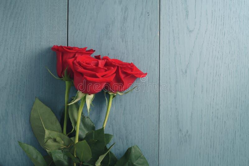 Drei rote Rosen auf Purplehearttabelle mit Kopienraum lizenzfreie stockfotos
