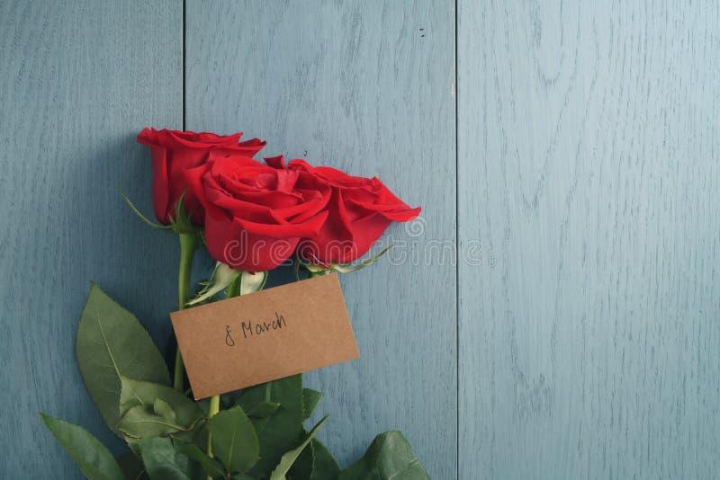 Drei rote Rosen auf Purplehearttabelle mit am 8. März Papierkarte stockbild