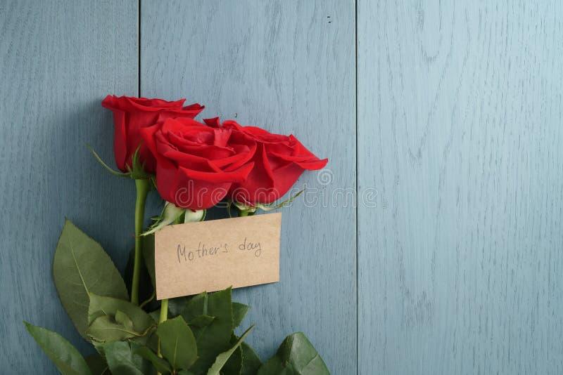 Drei rote Rosen auf Purplehearttabelle mit Muttertagespapierkarte stockbild