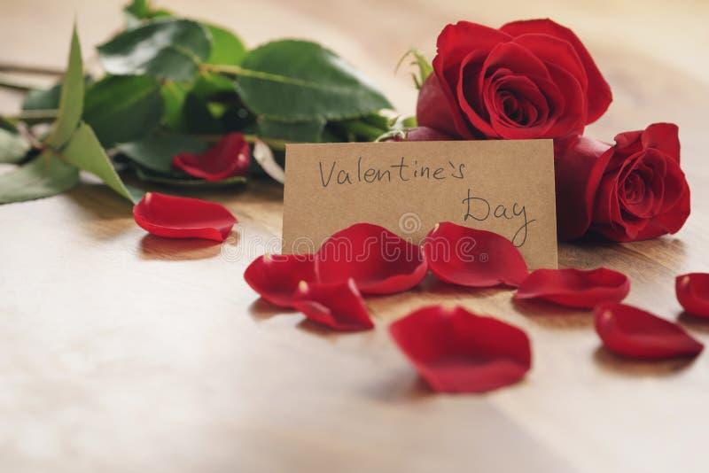 Drei rote Rosen und Blumenblätter auf alter hölzerner Tabelle mit Papierkarte für Valentinsgrußtag lizenzfreie stockfotografie