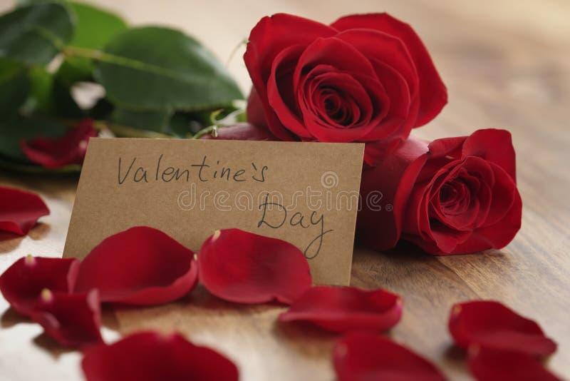 Drei rote Rosen und Blumenblätter auf alter hölzerner Tabelle mit Papierkarte für Valentinsgrußtag stockbild