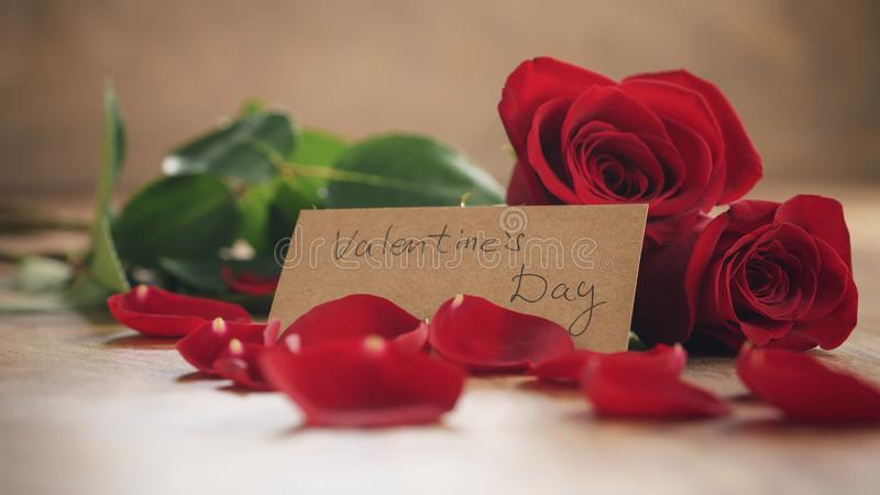 Drei rote Rosen und Blumenblätter auf alter hölzerner Tabelle mit Papierkarte für Valentinsgrußtag stockfoto