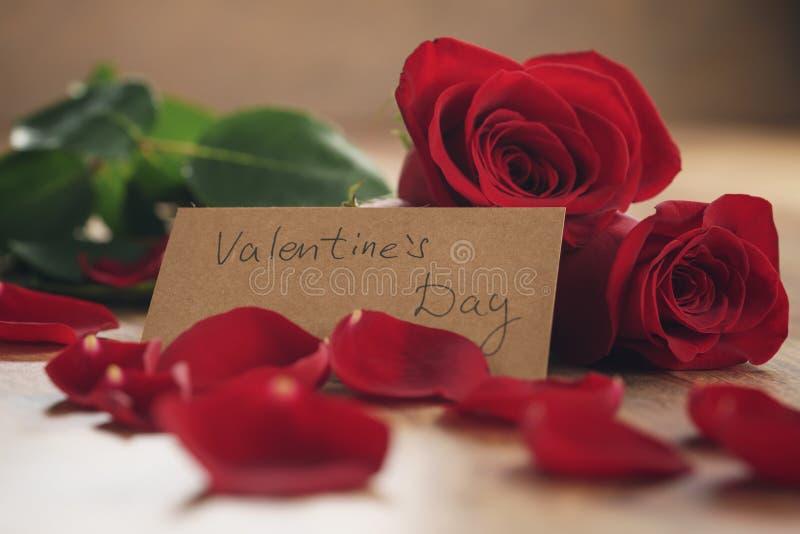Drei rote Rosen und Blumenblätter auf alter hölzerner Tabelle mit Papierkarte für Valentinsgrußtag lizenzfreies stockbild