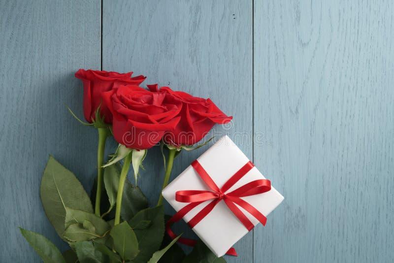 Drei rote Rosen und eine Geschenkbox auf Purplehearttabelle mit Kopienraum stockbild