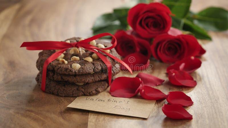 Drei rote Rosen und selbst gemachte Plätzchen auf alter hölzerner Tabelle mit Papierkarte für Valentinsgrußtag lizenzfreies stockbild