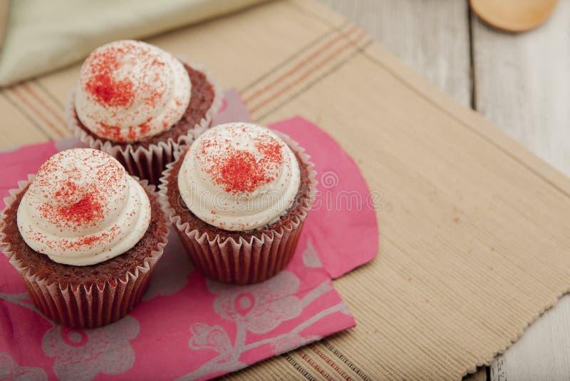 Drei rote Samtkleine kuchen auf bunter Tüte lizenzfreies stockfoto